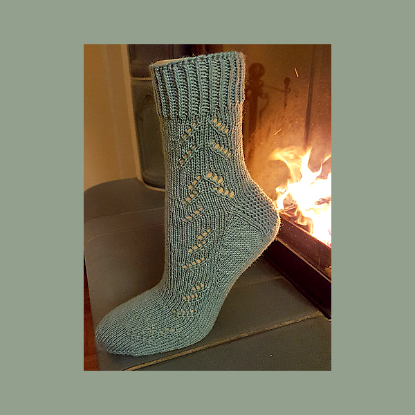 A modelled Giuthas sock knit in olive green yarn on a sock form in front of a fire place