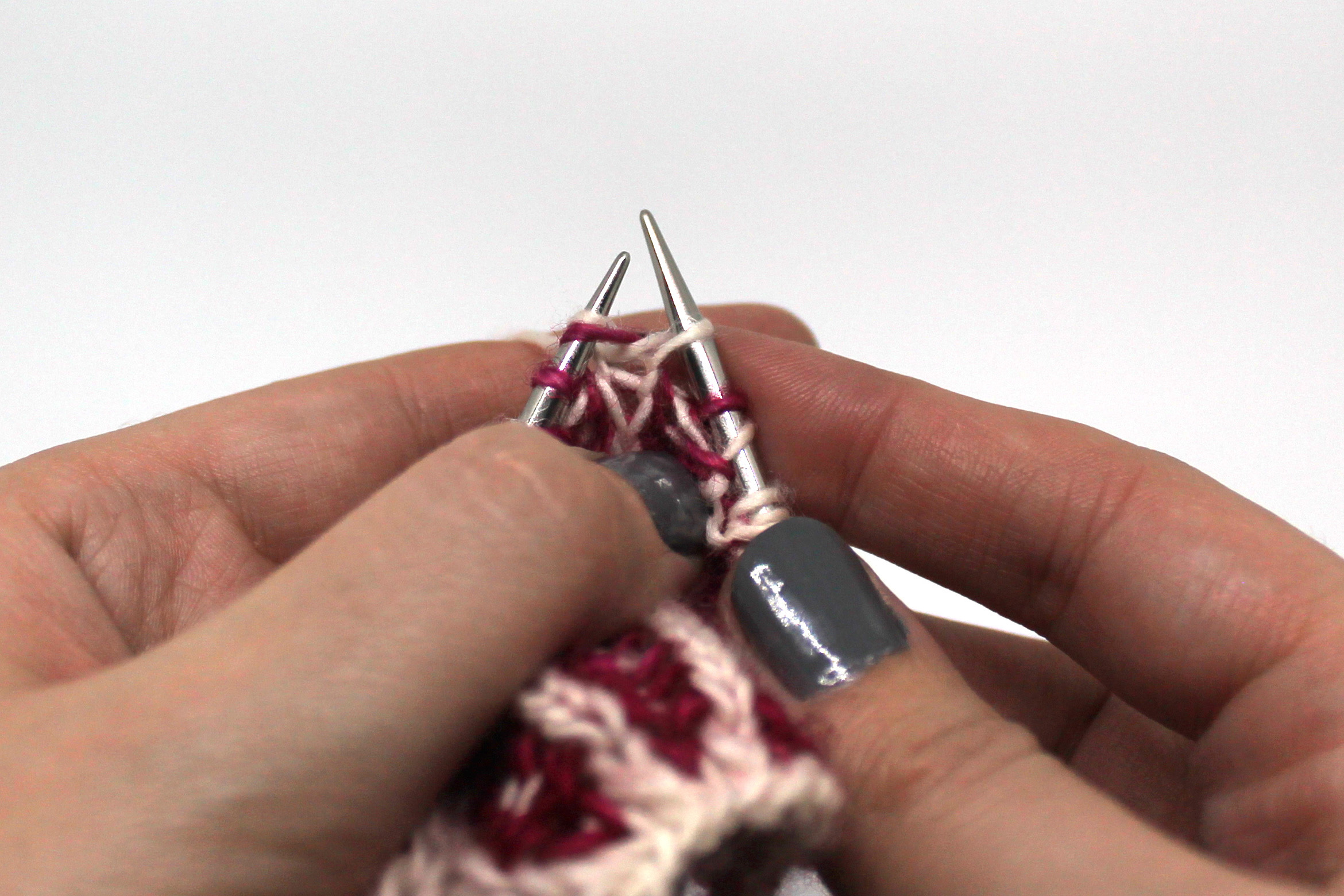A stitch on the left hand needle with a knit stitch through it on the right hand needle