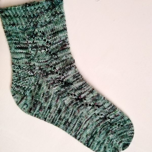 A Giuthas sock knit in green speckled yarn on a sock blocker