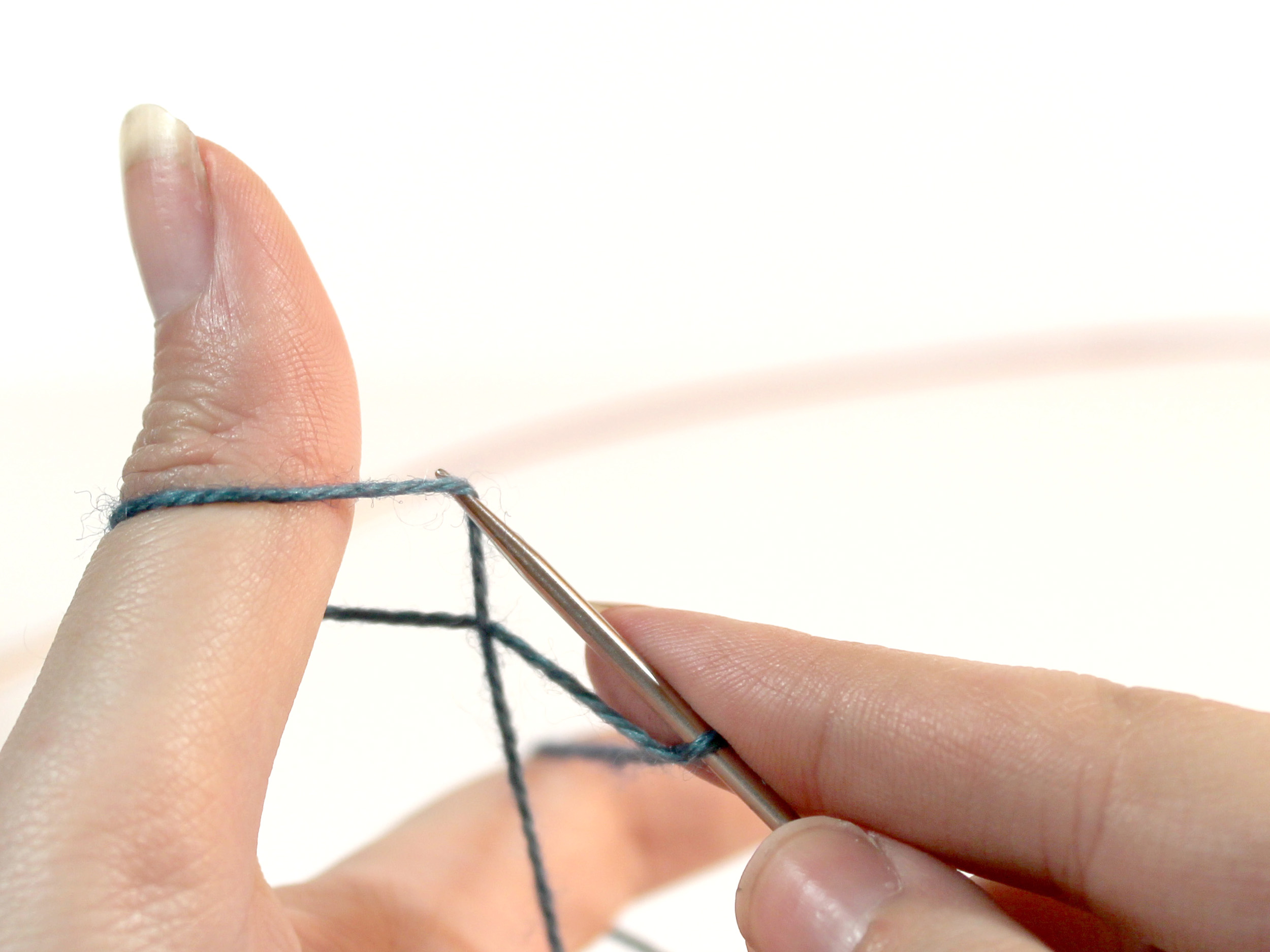 The knitting needle is lifting the strand of yarn that runs from the ring finger to the thumb on it's tip.