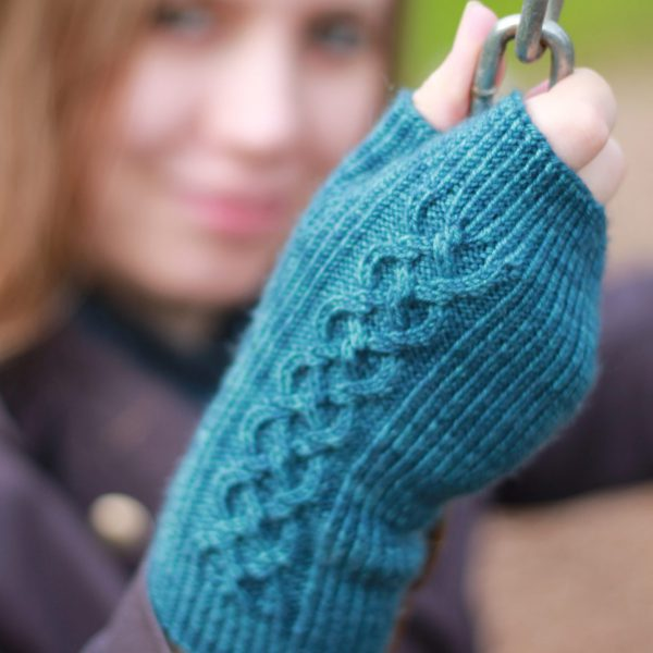 Twisted rib fingerless mitts with a large cable up the back of the hand and a narrow cable pattern that splits around the thumb