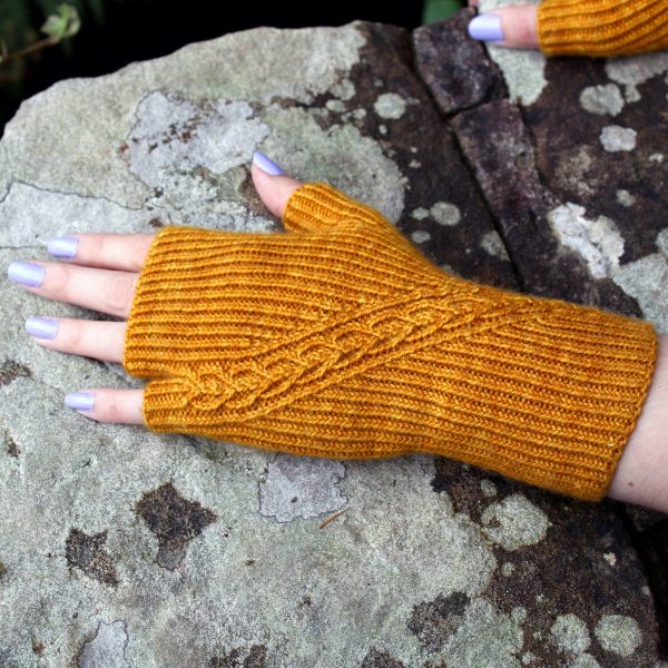 Twisted rib fingerless mitts with a narrow cable crossing the back of the hand from the inside of the wrist to the little finger. The little finger has a separate opening.