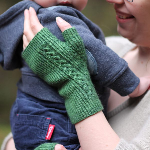 Twisted rib fingerless mitts with a large cable up the back of the hand and a narrow cable pattern that splits around the thumb (the model is holding a baby)