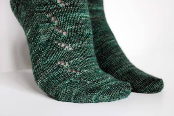 A close up on the foot of a modelled pair of socks in dark green with a lace pattern representing half a fir tree on the foot