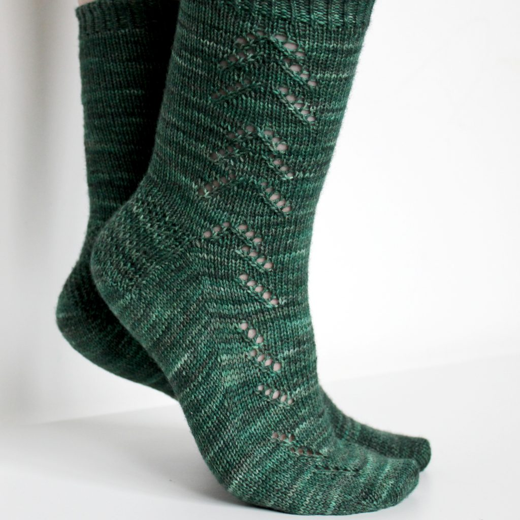 A modelled pair of socks in dark green with a lace pattern representing half a fir tree on the foot and a whole fir tree on the leg