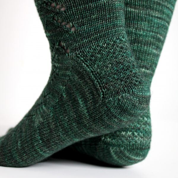 A close up on the textured heel pattern of a modelled pair of socks in knit dark green