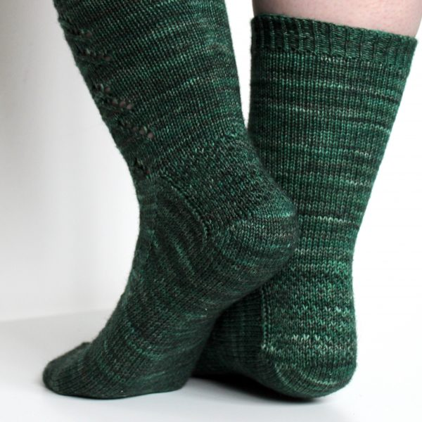 The back of the legs and textured heel pattern of a modelled pair of socks in knit dark green