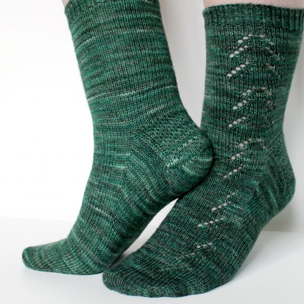 A close up on a sock knit in dark green with a lace pattern representing a whole fir tree on the leg