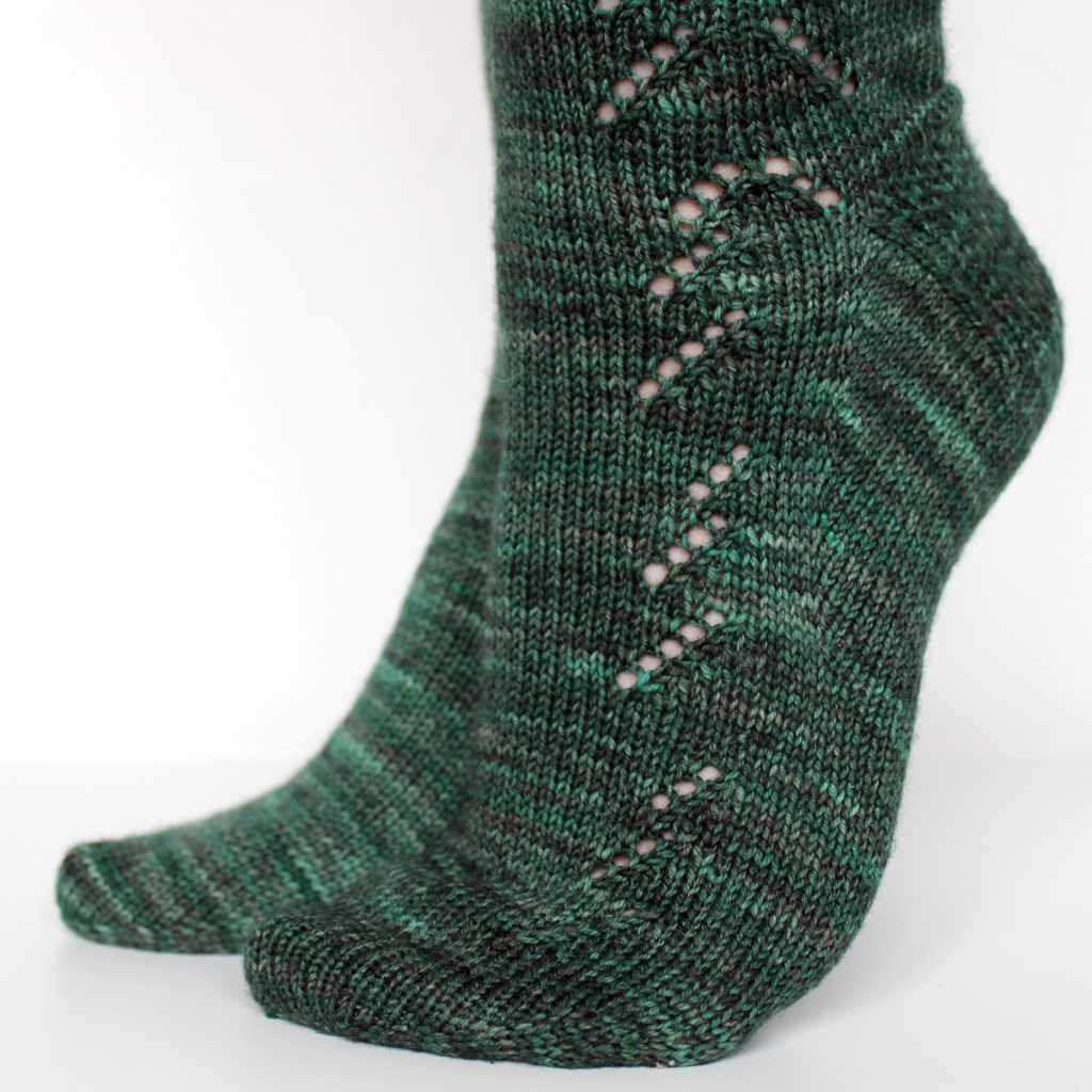 A close up on the foot of a modelled pair of socks in dark green with a lace pattern representing half a fir tree on the foot and a whole fir tree on the leg