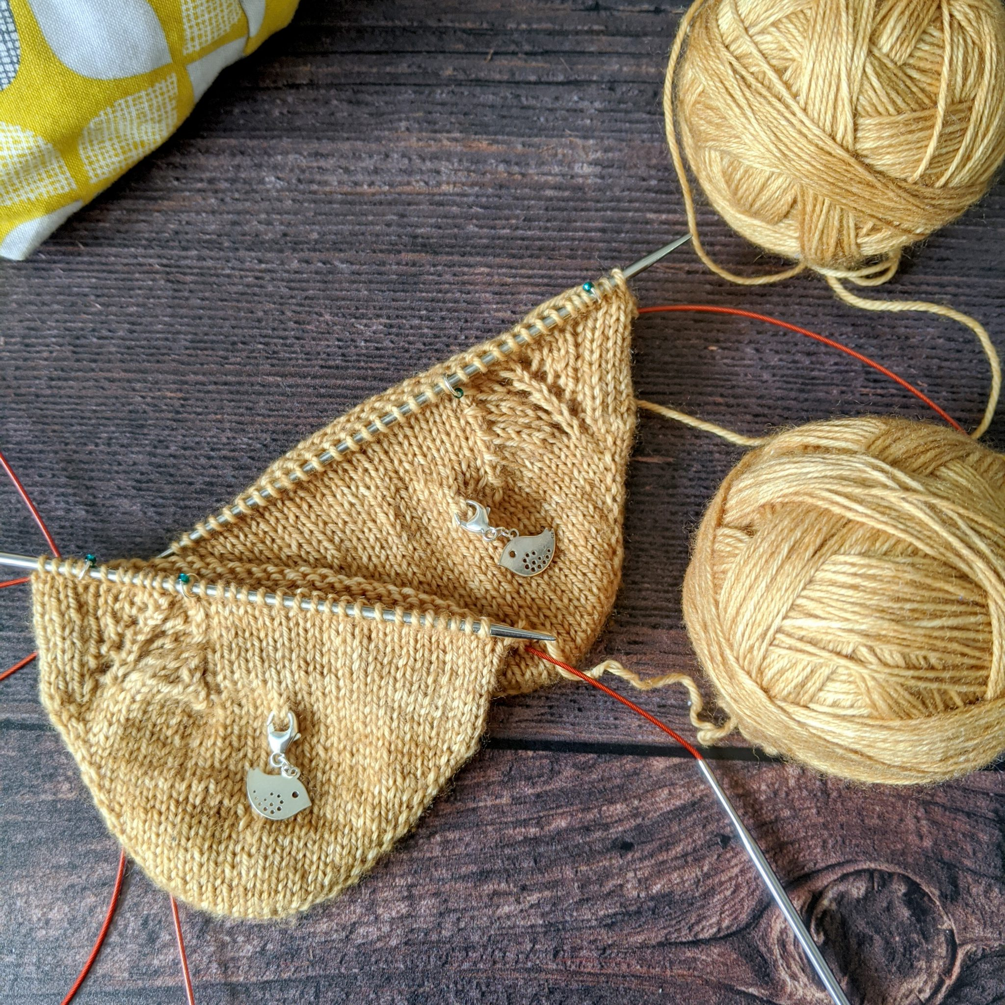 The toes of two socks in progress, they have a lace pattern and visible vertical line of decreases