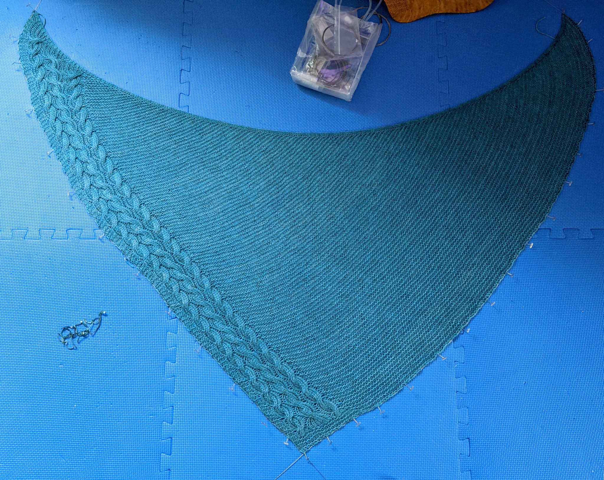 A photo showing the shawl during blocking