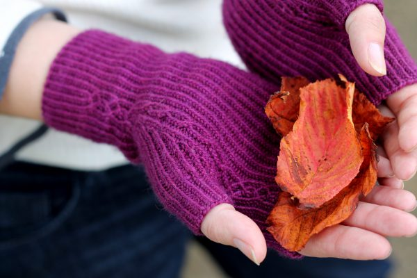 Twisted rib fingerless mitts with a narrow cable pattern that splits around the thumb (the model is holding bright autumn leaves)