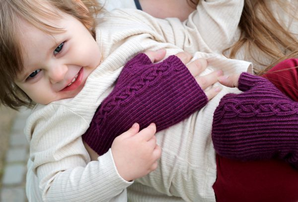 Twisted rib fingerless mitts with a large cable up the back of the hand and a narrow cable pattern that splits around the thumb (the model is holding a little girl)