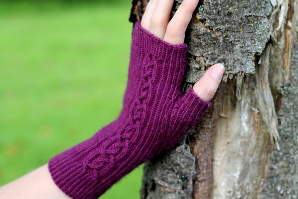 Twisted rib fingerless mitts with a large cable up the back of the hand and a narrow cable pattern that splits around the thumb (against a tree)