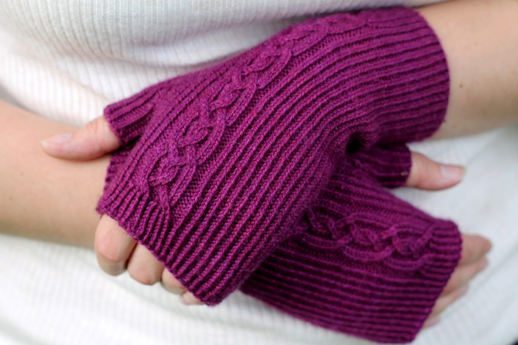 Twisted rib fingerless mitts with a large cable up the back of the hand and a narrow cable pattern that splits around the thumb (hands crossed)