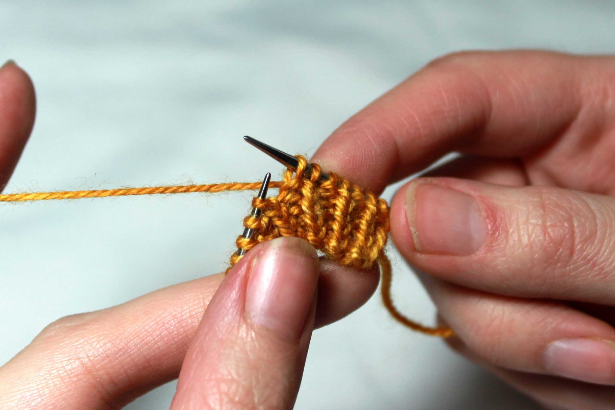 A piece of knitting in twisted rib. A purl stitch has been slipped from the left-hand needle to the right-hand needle
