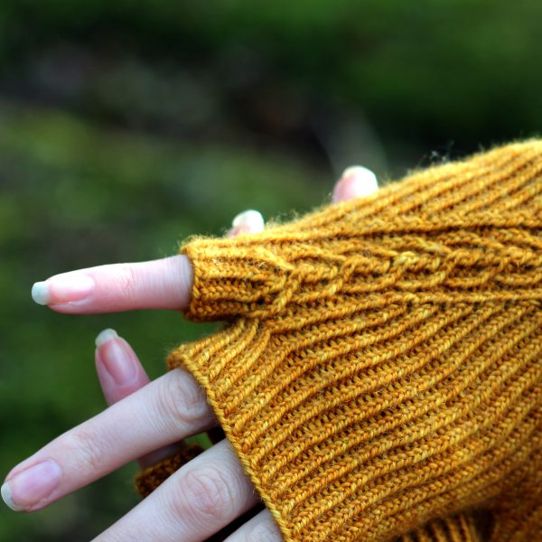 Twisted rib fingerless mitts with a narrow cable crossing the back of the hand from the inside of the wrist to the little finger. The little finger has a separate opening. A close up of the little finger detail