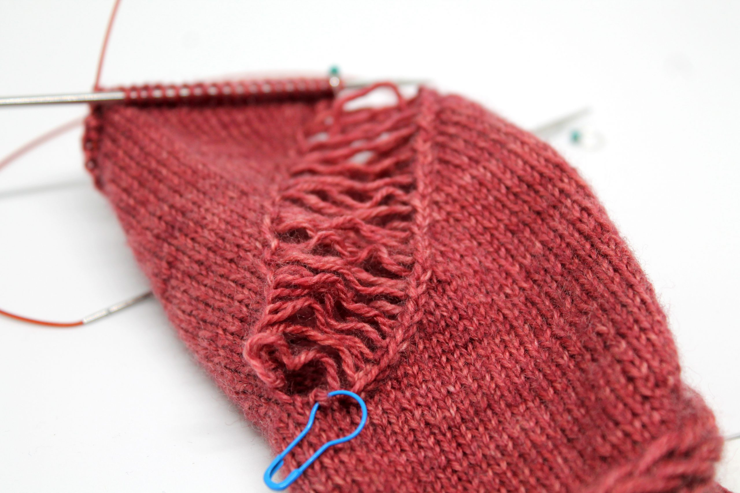A piece of knitting with a wide laddered gap where stitches have been dropped. At the bottom of the photo is a stitch with a bulb stitch marker through it.