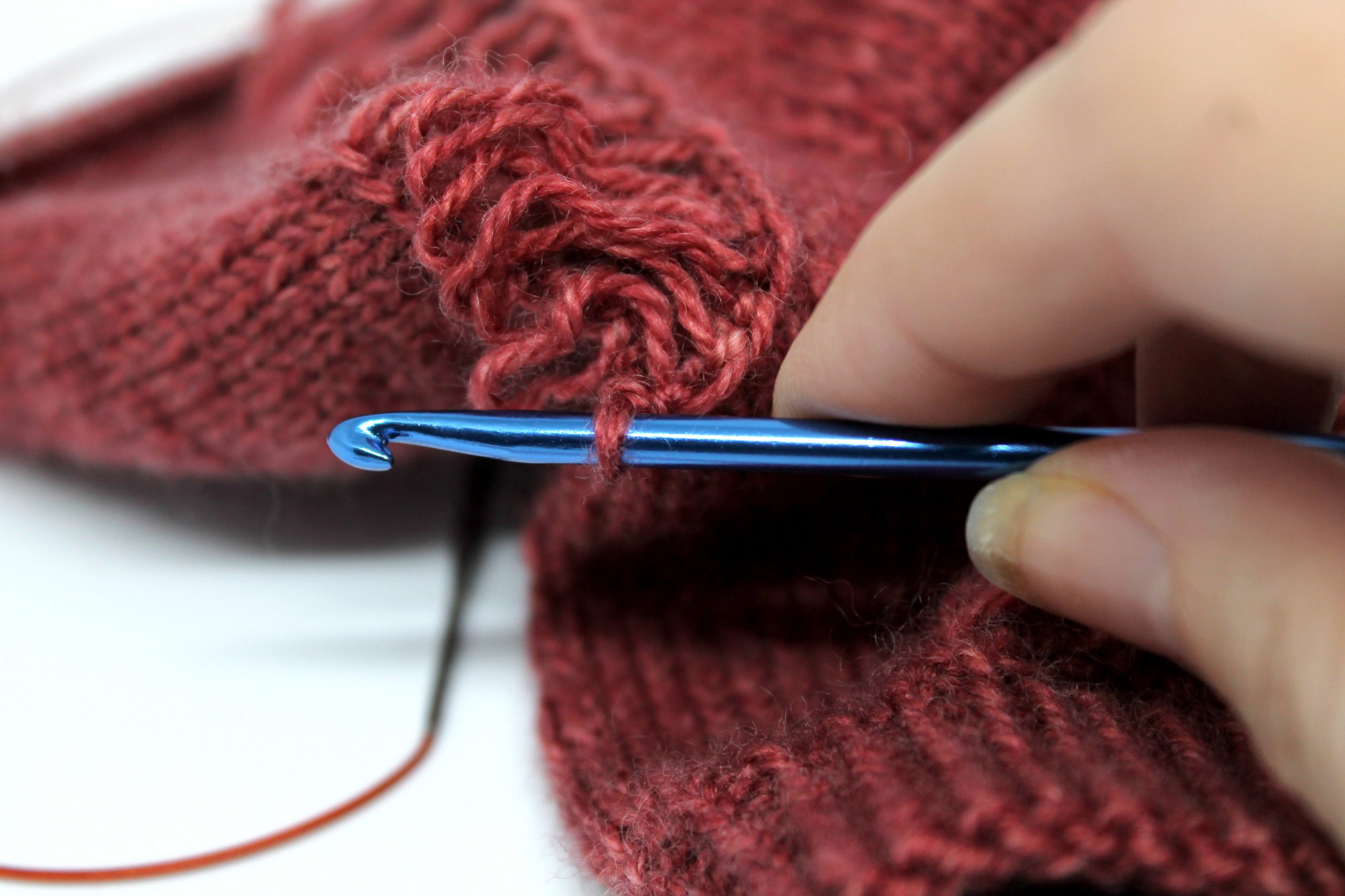 The stitch with the removable marker has now been place on a crochet hook, and the stitch marker removed. The laddered dropped stitches can still be seen at the back of the photo