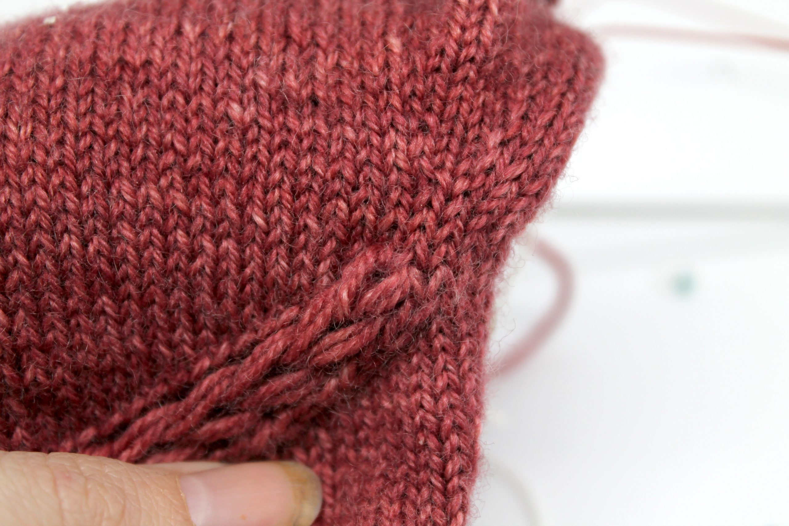A close up on the finished drop stitch braid showing how it meets the knitting above showing several rows of stitching stitch above the finished braid