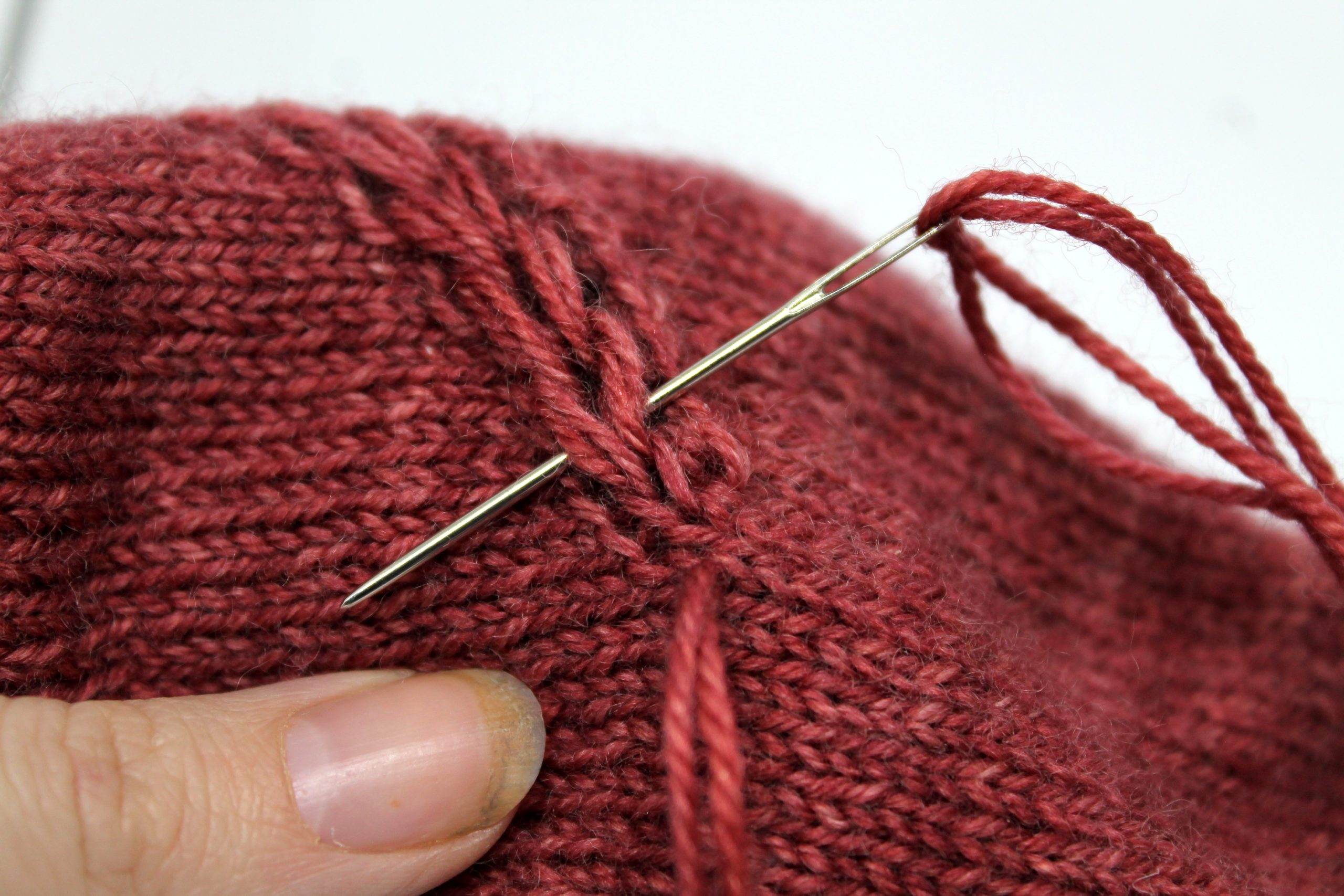 The tapestry needle passing behind the first stitch of the drop stitch braid