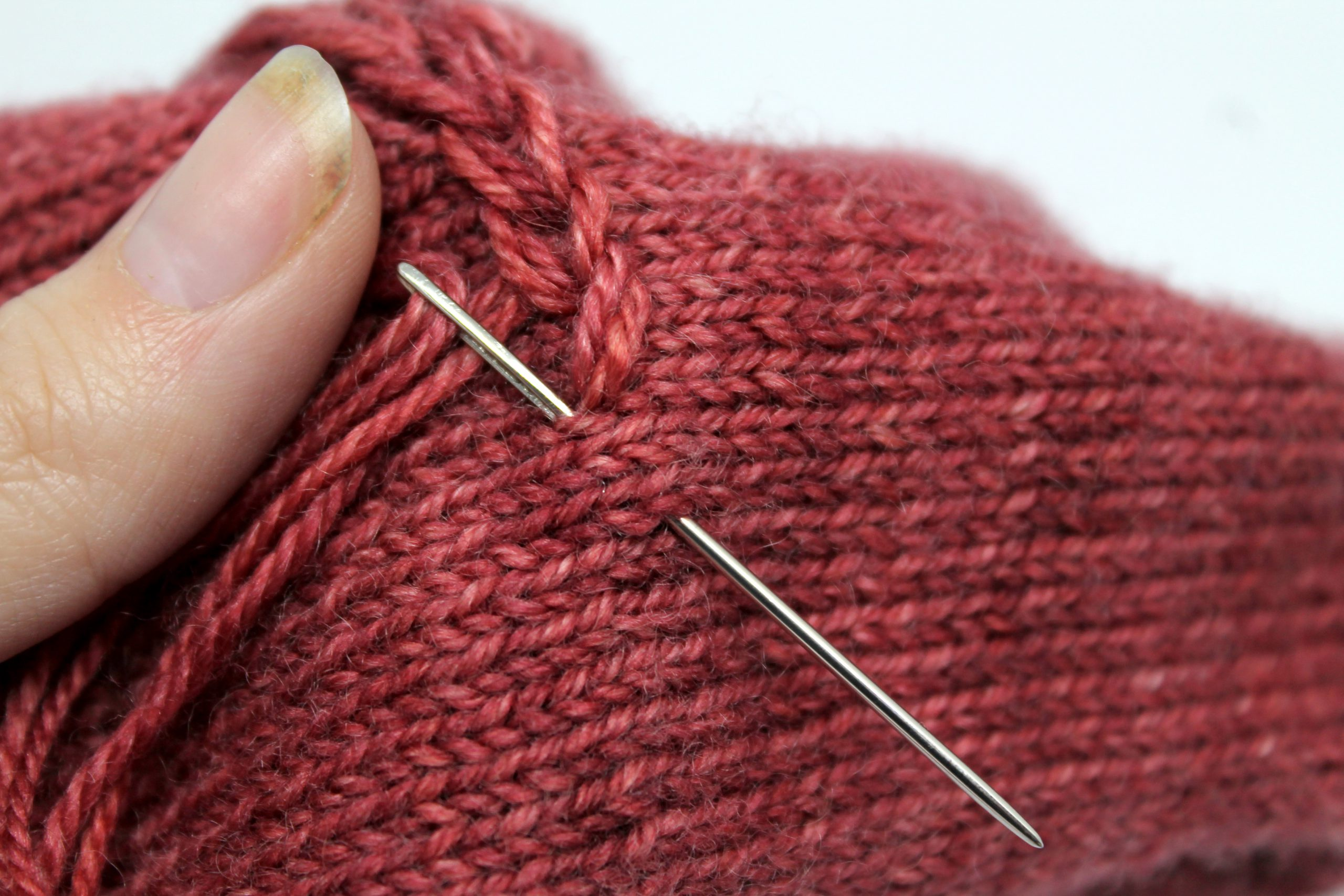 A tapestry needle entering and exiting the fabric of the mitt to finish one chain stitch and start the next