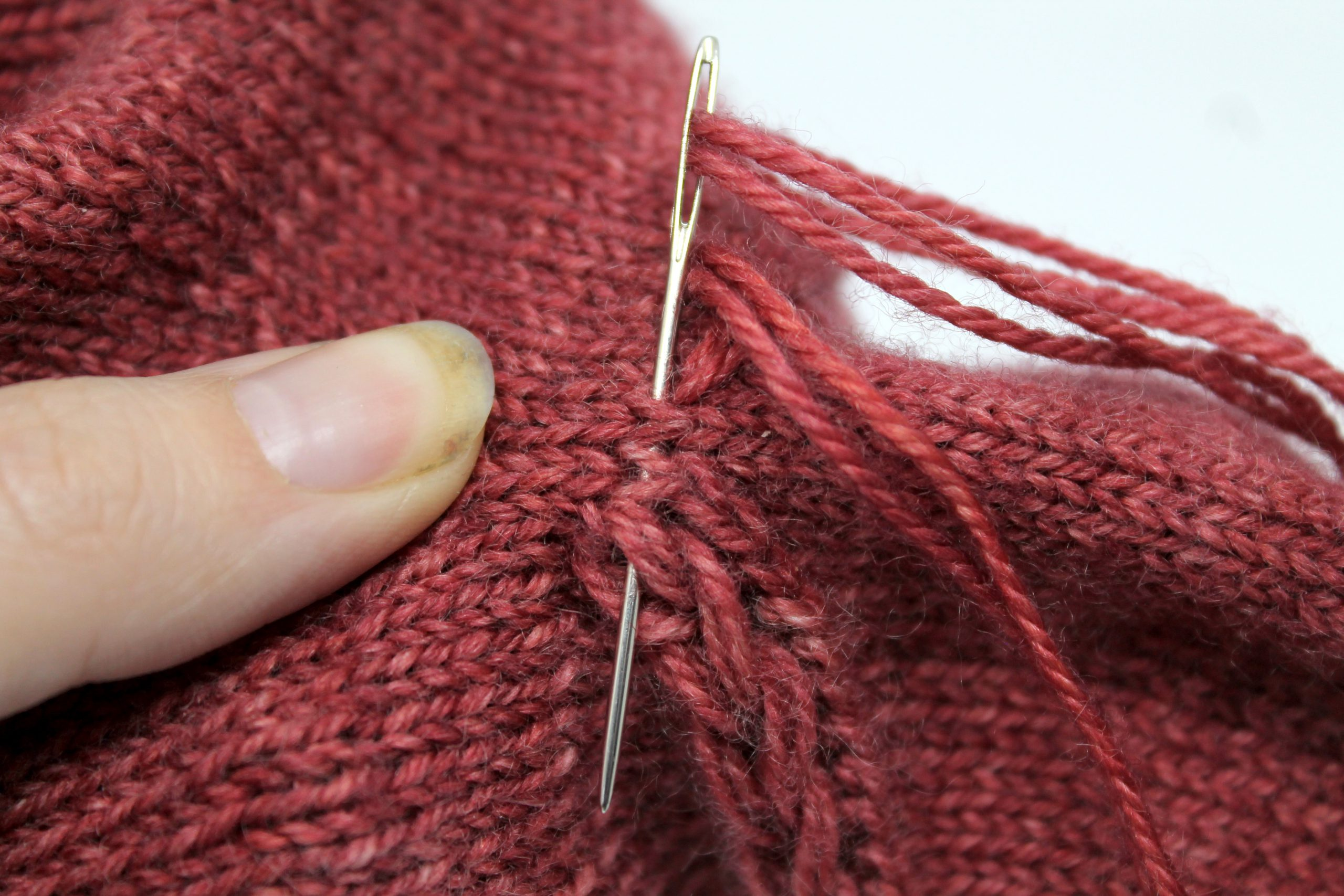 The tapestry need entering the mitt through the fabric and exiting through the last stitch of the drop stitch braid