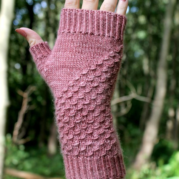 A fingerless mitt knit in pink yarn with a textured pattern travelling diagonally across the back of the hand.