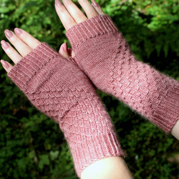 Fingerless mitts knit in pink yarn with a textured pattern travelling diagonally across the back of each hand.