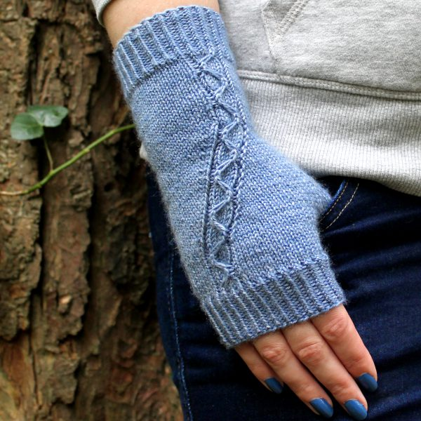 A blue fingerless mitt with a cable pattern travelling diagonally across the back of the hand, with the thumb tucked into the pocket of a pair of jeans