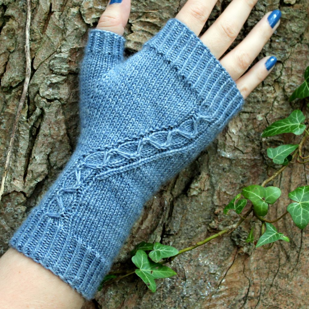 A blue fingerless mitt with a cable pattern travelling diagonally across the back of the hand, laid against an ivy covered tree