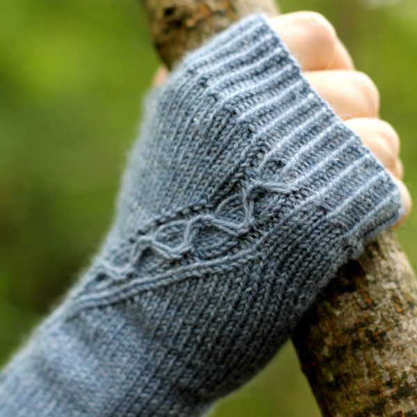 A blue fingerless mitt with a cable pattern travelling diagonally across the back of the hand, showing the detail of the cable meeting the cuff, with the hand holding a tree branch