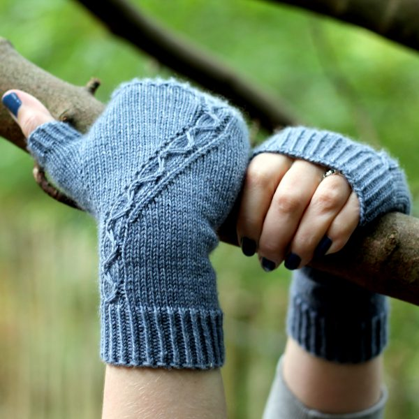 A blue fingerless mitt with a cable pattern travelling diagonally across the back of the hand, with both hands holding a tree branch
