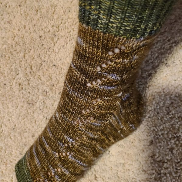 A modelled Giuthas sock knit in brown speckled yarn with contrast toe and cuff in green yarn on a sock blocker
