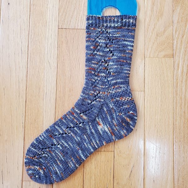 A Giuthas sock knit in blue speckled yarn on a sock blocker