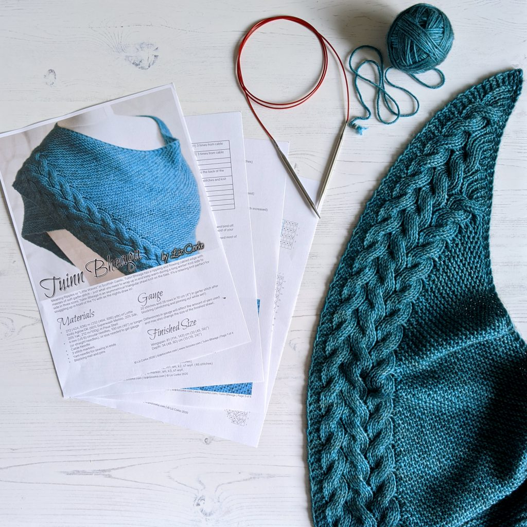 A knitting pattern with a ball of yarn, knitting needles and part of the shawl made form the pattern