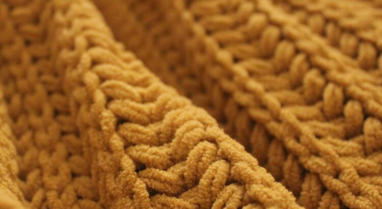 A piece of knitting in yellow yarn