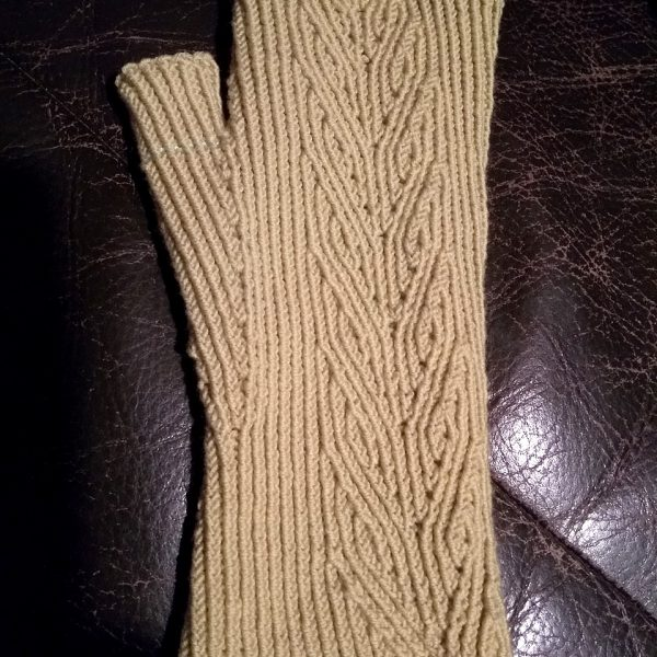 A light coloured fingerless mitt with twisted rib and a faux cable pattern, against a dark leather background