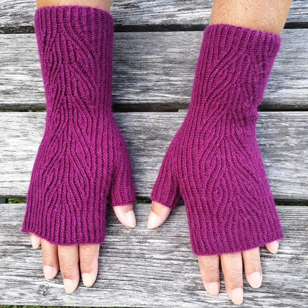 A pair of purple fingerless mitts with twisted rib and a faux cable pattern, against a grey wooden background