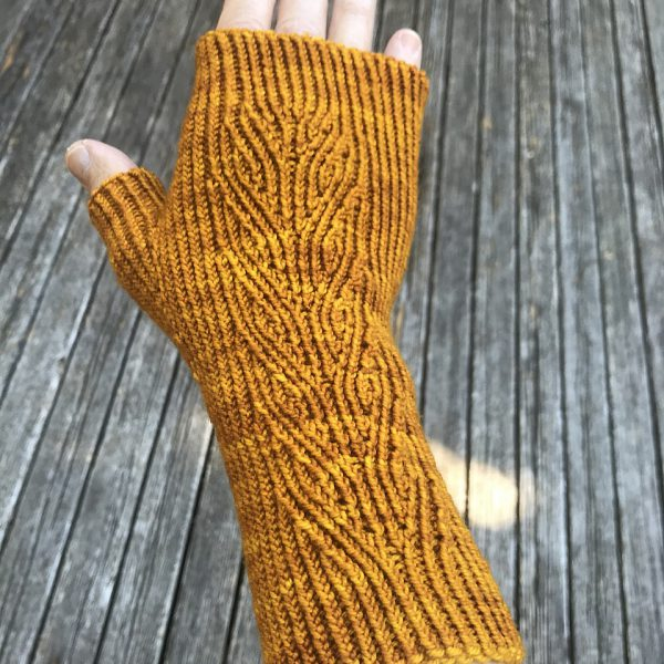 A golden fingerless mitt with twisted rib and a faux cable pattern, against a wooden background