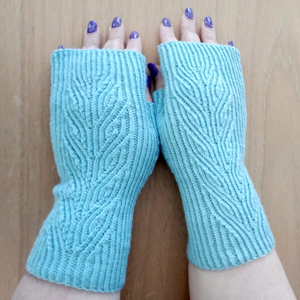 A pair of light blue fingerless mitts with twisted rib and a faux cable pattern, against a wooden background