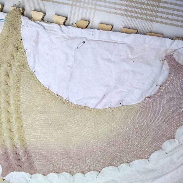 A white asymmetrical garter stitch shawl with a reversible cable pattern down one edge during blocking