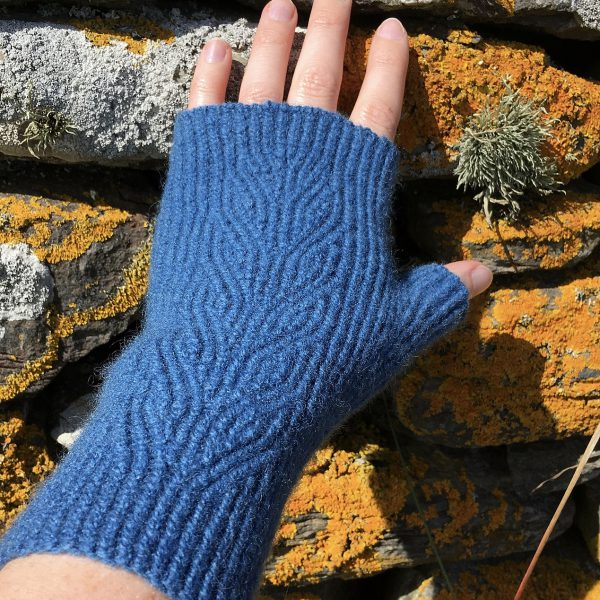 A dark blue fingerless mitt with twisted rib and a faux cable pattern, against a dry stone wall