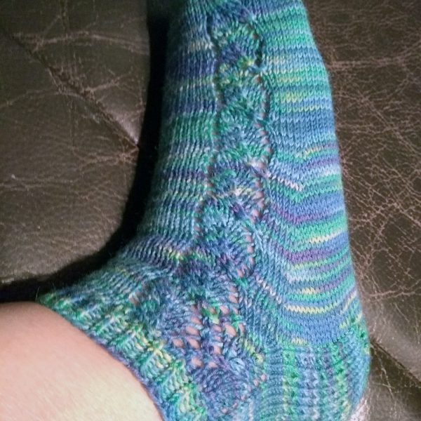 A sock with a lace leaf pattern up the outside of the foot knitted in variegated blue and purple yarn
