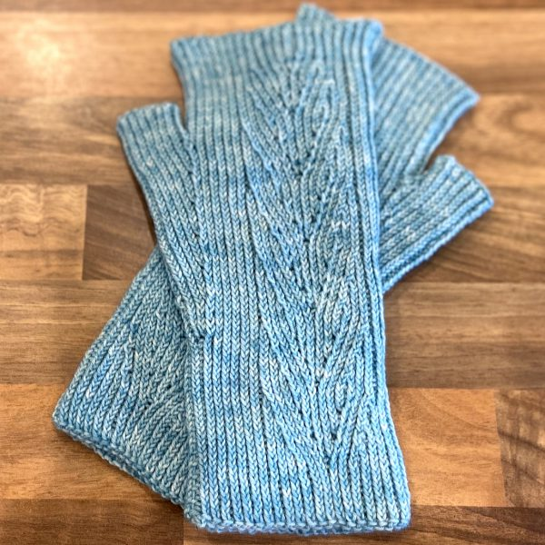 A pair of light blue fingerless mitts with twisted rib and a faux cable pattern, laid flat on a wooden surface