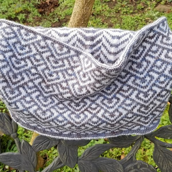 """A cowl with stranded knitting in speckled grey and white yarn with a pattern made up of interlocking """"V"""" shapes and scale shapes, over the back of a chair. You can see a colourwork pattern of soft curves on the inside"""