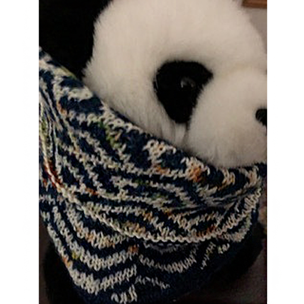 """A cowl with stranded knitting in blue and white speckled yarn with a pattern made up of interlocking """"V"""" shapes and scale shapes, modelled by a toy panda"""
