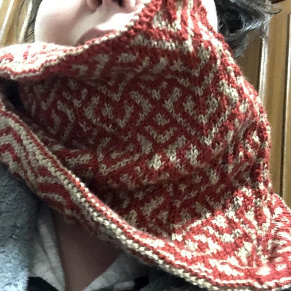 """A cowl with stranded knitting in red and gold yarn with a pattern made up of interlocking """"V"""" shapes and scale shapes, modelled by a woman"""