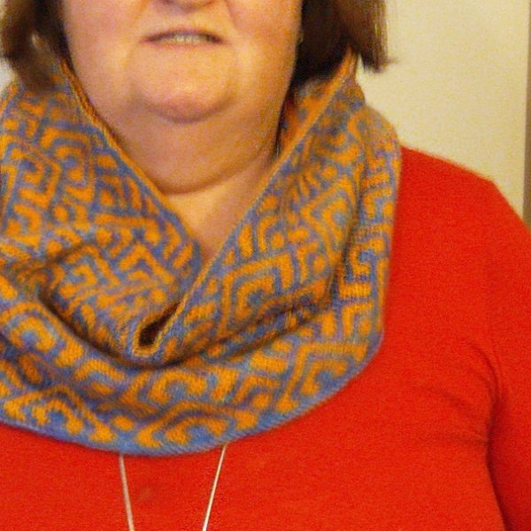 """A cowl with stranded knitting in orange and blue yarn with a pattern made up of interlocking """"V"""" shapes and scale shapes, modelled woman in a red top"""