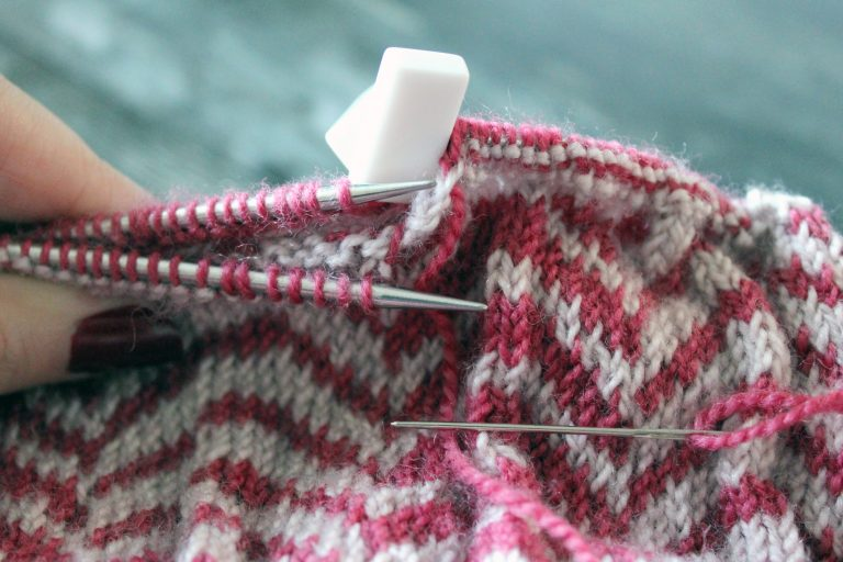 """A piece of colourwork knitting ready to be grafted. There are stitches on two needles held parallel to each other and referred to as """"front needle"""" and """"back needle"""". There is an embroidery needle with the yarn tail threaded through it. The ends of the circular needles have white stoppers to prevent the stitches coming off the end."""